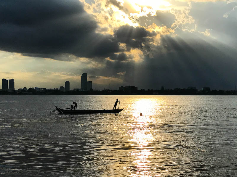 Cambodia family holiday highlights - the beauty of a sunset on a simple fishing boat on the Mekong river